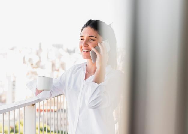 Retrato de una mujer sonriente que sostiene la taza de café que habla en el teléfono móvil Foto gratis