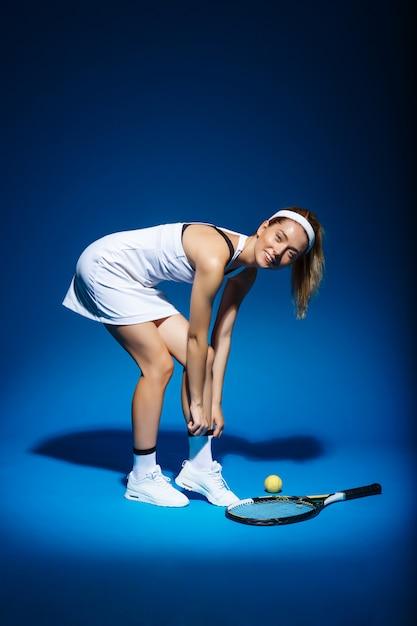 Retrato de mujer tenista con raqueta y pelota a un lado Foto gratis