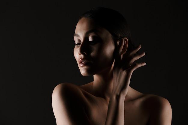 Retrato de mujer tierna femenina con mirada sensual mirando a un lado con poca luz, aislado sobre negro Foto gratis
