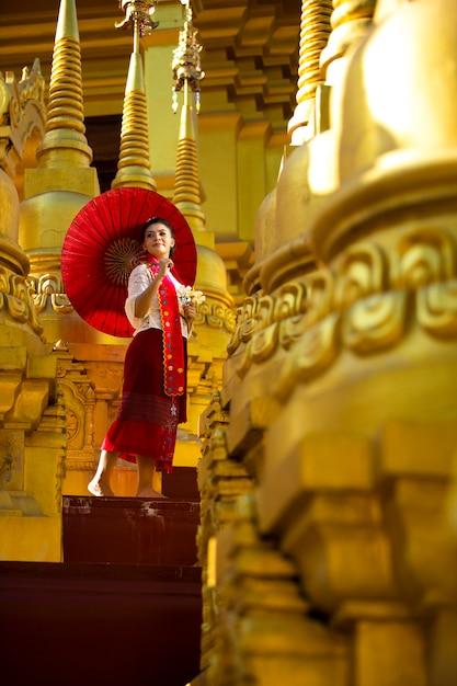 Retrato de una mujer en traje nacional birmano de pie con un paraguas rojo en medio de muchas pagodas doradas Foto Premium