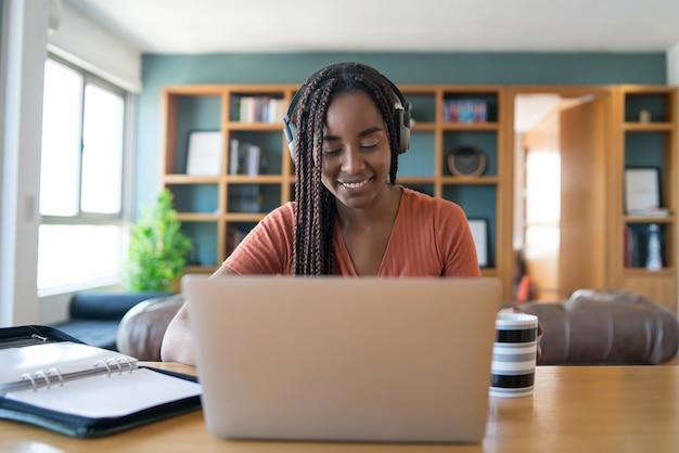 Retrato de una mujer en una videollamada con una computadora portátil y auriculares mientras trabaja desde el concepto de hogar Foto gratis