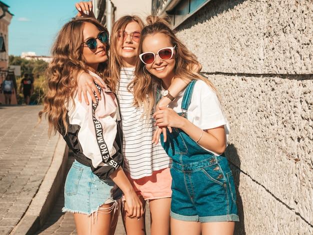 Retrato de mujeres despreocupadas sexy posando en la calle cerca de la pared. modelos positivos divirtiéndose en gafas de sol. Foto gratis