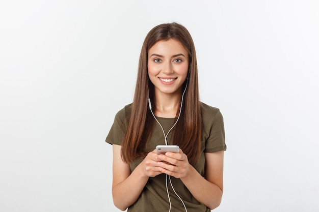 Retrato de una música que escucha alegre linda de la mujer en auriculares y baile aislado en un blanco. Foto Premium