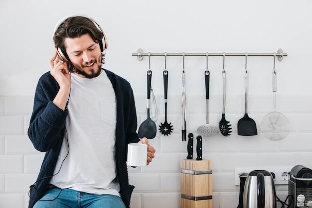 Retrato de una música que escucha del hombre en el auricular que se sienta en el contador de la cocina Foto gratis