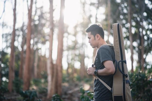 Retrato músico hombre con guitarra en el bosque Foto Premium
