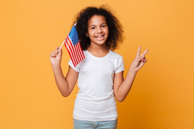 Retrato de una niña africana feliz con bandera americana Foto gratis