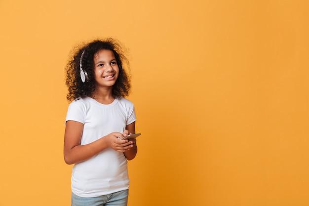Retrato de una niña africana feliz escuchando música Foto gratis
