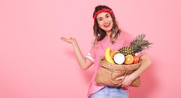 Retrato de una niña con una bolsa con fruta aislado en una pared rosa Foto gratis