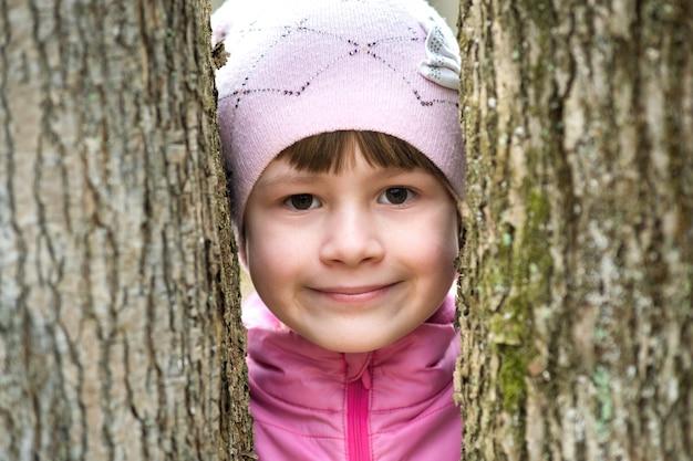 Retrato de niña bonita joven vistiendo chaqueta rosa y gorra de pie entre los árboles Foto Premium