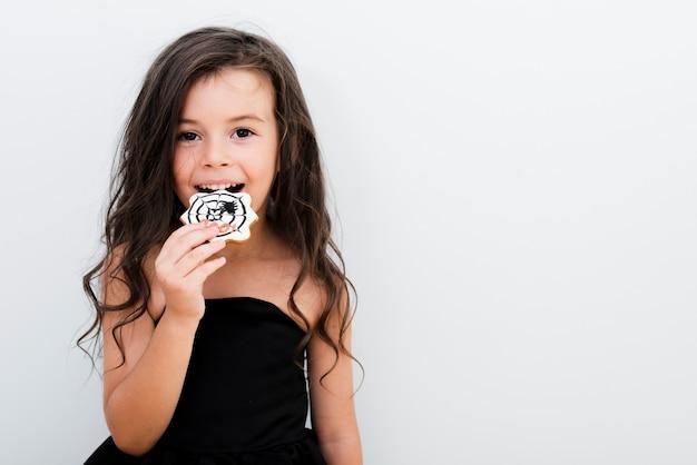 Retrato de una niña comiendo una galleta Foto gratis