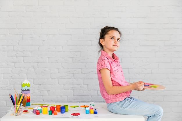 Retrato de una niña contemplada sentada en la mesa blanca mezclando la acuarela en la paleta Foto gratis