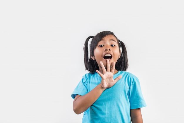 Retrato de la niña divertida que actúa en tiro del estudio Foto gratis