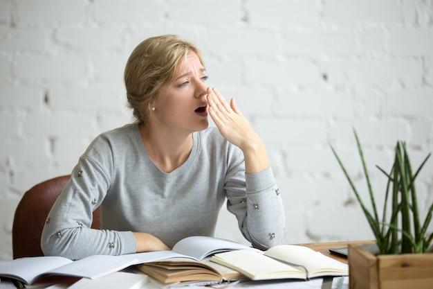 Retrato de una niña estudiante bostezar en el escritorio Foto gratis