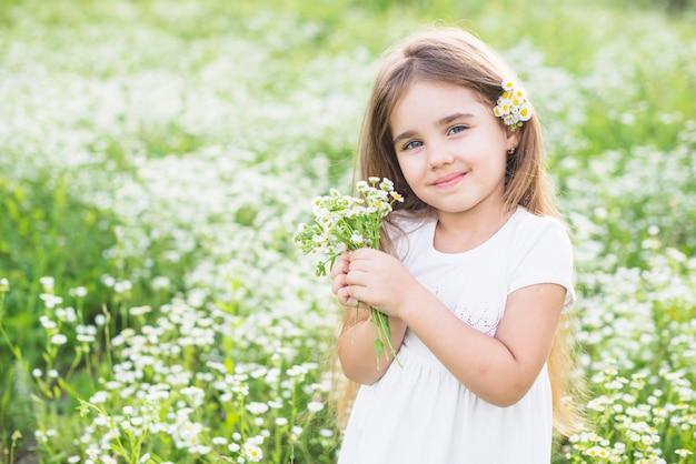 Retrato de niña feliz con flores blancas en la mano Foto gratis
