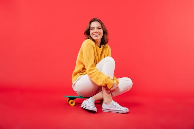 Retrato de una niña feliz sentada en una patineta Foto gratis