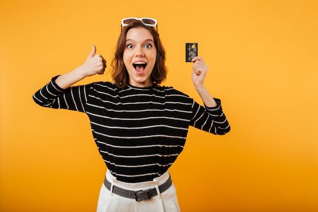 Retrato de una niña feliz con tarjeta de crédito Foto gratis
