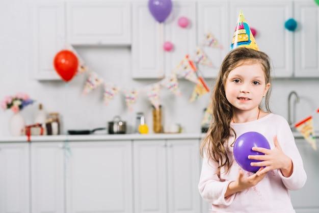 Retrato de una niña con globo morado de pie en la cocina Foto gratis