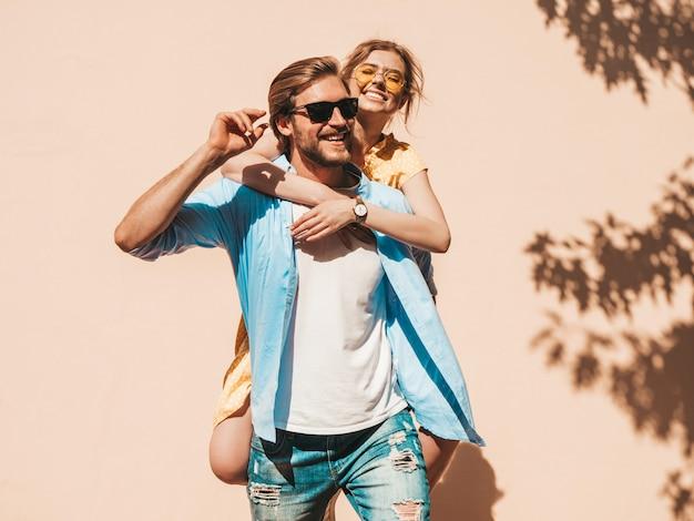 Retrato de niña hermosa sonriente y su novio guapo. mujer en vestido casual de verano y hombre en jeans. feliz familia alegre. mujer divirtiéndose en la calle cerca de la pared Foto gratis