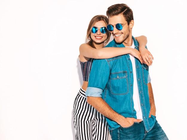 Retrato de niña hermosa sonriente y su novio guapo riendo. feliz pareja alegre en gafas de sol. Foto gratis