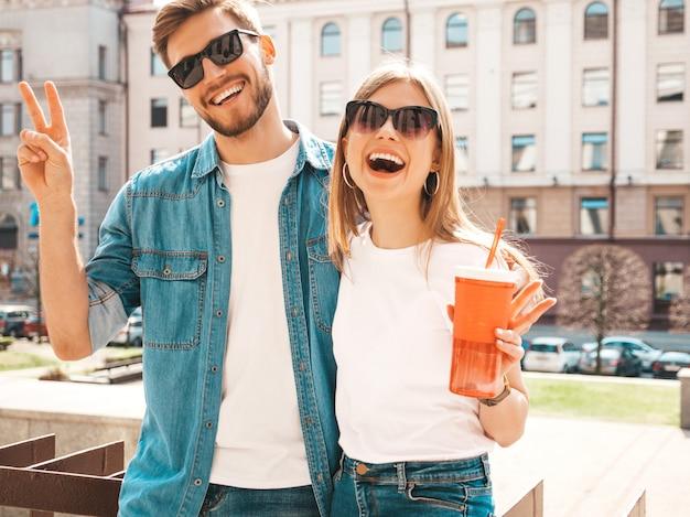 Retrato de niña hermosa sonriente y su novio guapo en ropa casual de verano. . con botella de agua y paja Foto gratis