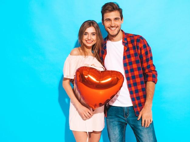 Retrato de niña hermosa sonriente y su novio guapo sosteniendo globos en forma de corazón y riendo. feliz pareja de enamorados. feliz día de san valentín. posando Foto gratis