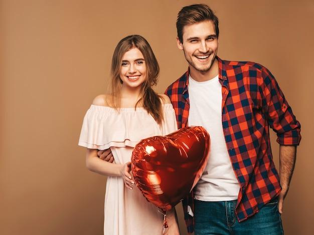 Retrato de niña hermosa sonriente y su novio guapo sosteniendo globos en forma de corazón y riendo. feliz pareja de enamorados. feliz día de san valentín Foto gratis