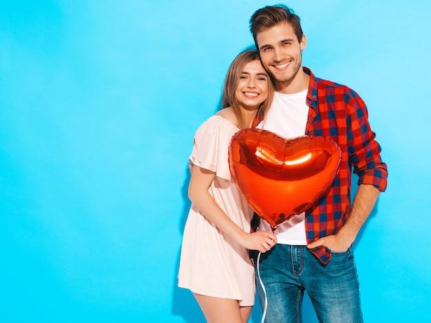 Retrato de niña hermosa sonriente y su novio guapo sosteniendo globos en  forma de corazón y riendo. feliz pareja de enamorados. feliz día de san  valentín | Foto Gratis