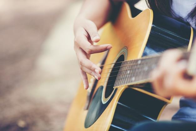 Retrato de niña hermosa tocando la guitarra con bicicleta en la naturaleza Foto gratis