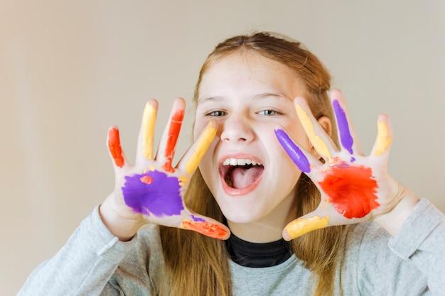 Retrato de una niña con las manos pintadas Foto gratis
