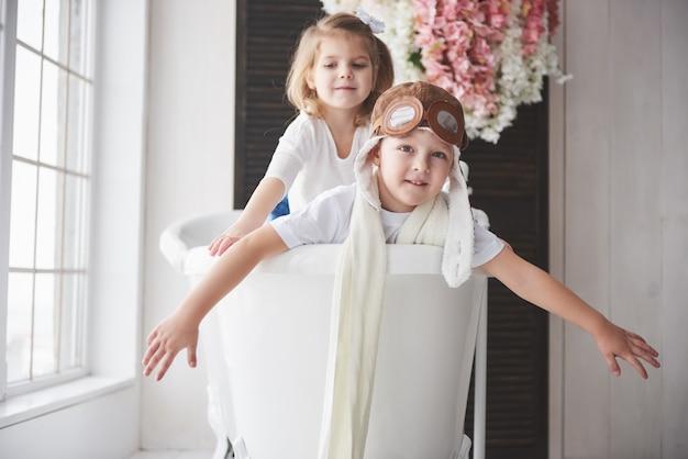 Retrato de una niña y un niño con sombrero de piloto jugando en el baño a los pilotos o marineros. viajes, infancia y realización de sueños. Foto Premium