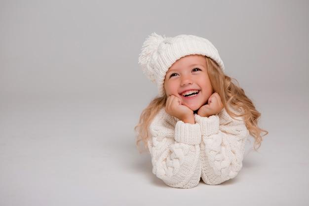 Retrato de una niña de pelo rizado en un gorro de invierno blanco de punto Foto Premium
