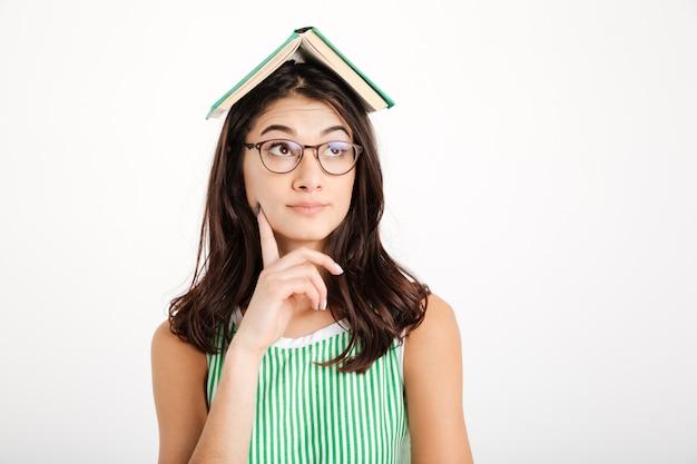 Retrato de una niña pensativa en vestido y anteojos Foto gratis