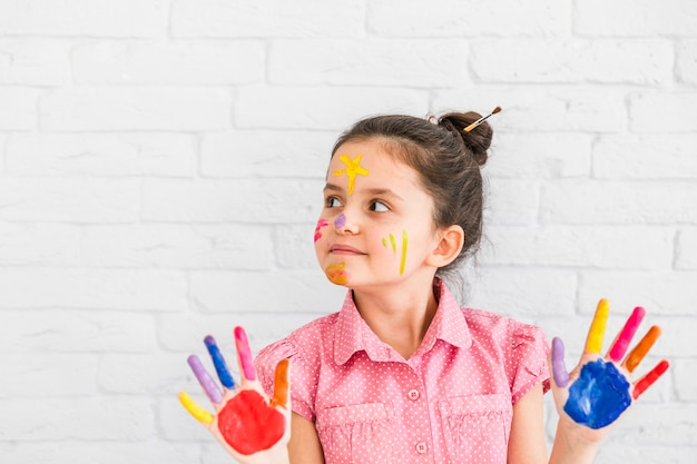 Retrato de una niña de pie contra la pared blanca que muestra las manos pintadas de colores mirando a otro lado Foto gratis