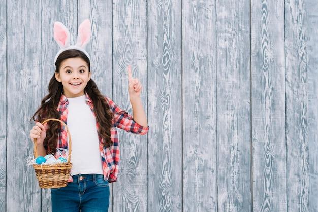 Retrato de una niña que sostiene la cesta de los huevos de pascua que señala el dedo hacia arriba contra fondo de madera Foto gratis