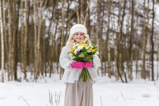 Retrato de una niña con un ramo de flores en el bosque en invierno Foto Premium