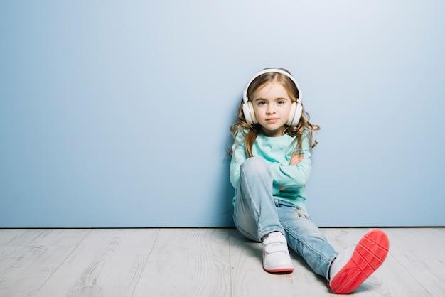 Retrato de una niña sentada contra azul con auriculares en su cabeza escuchando música Foto gratis