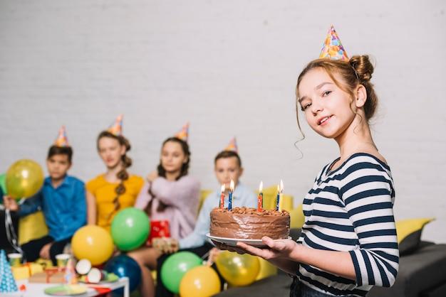 Retrato de una niña sonriente con pastel de cumpleaños con amigos en el fondo Foto gratis