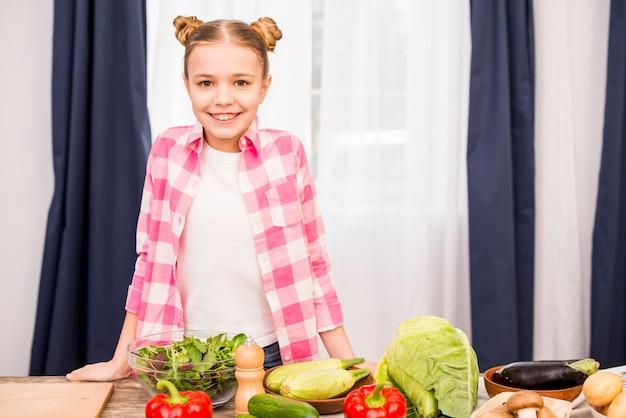 Retrato de una niña sonriente de pie detrás de la mesa con verduras frescas Foto gratis