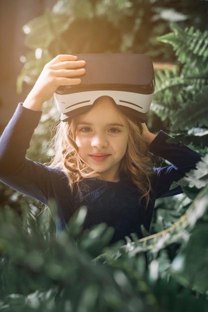 Retrato de una niña sonriente de pie entre las plantas con gafas de realidad virtual en la cabeza Foto gratis