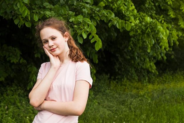 Retrato de niña sonriente posando en el parque Foto gratis