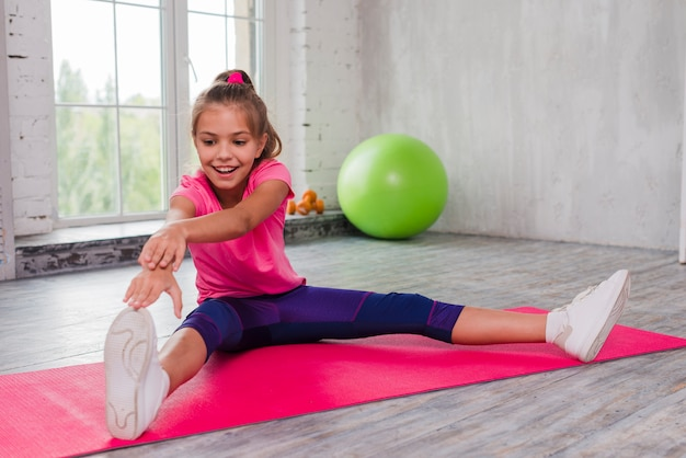 Retrato de una niña sonriente sentada en una estera de ejercicios estirando su mano y pierna Foto gratis