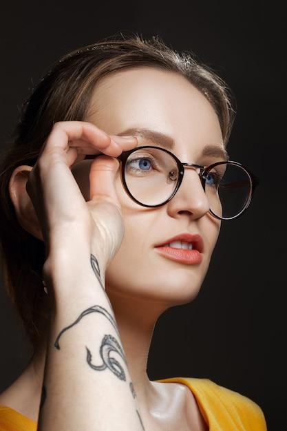 Retrato de niña sospechosa con tatuaje en su brazo. Foto Premium