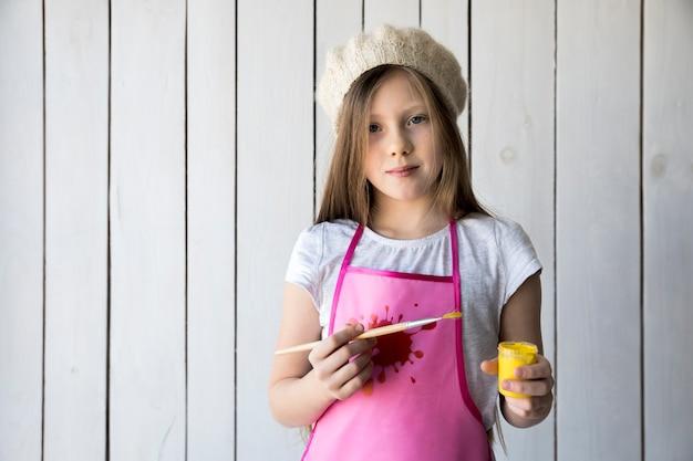 Retrato de una niña sosteniendo un pincel y una botella de pintura amarilla en la mano de pie contra la pared de madera blanca Foto gratis