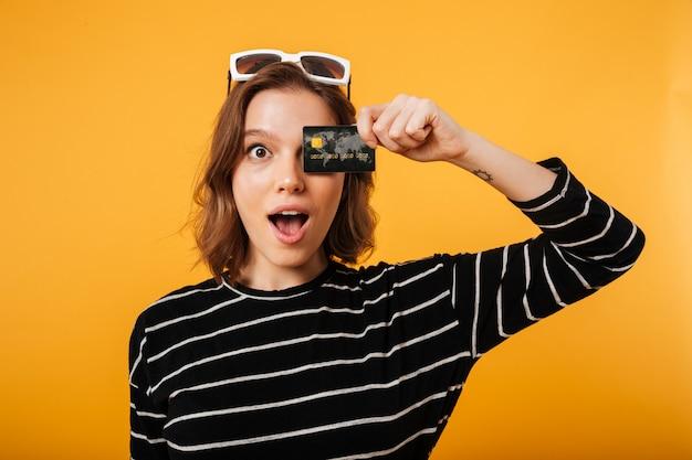 Retrato de una niña con tarjeta de crédito en la cara Foto gratis