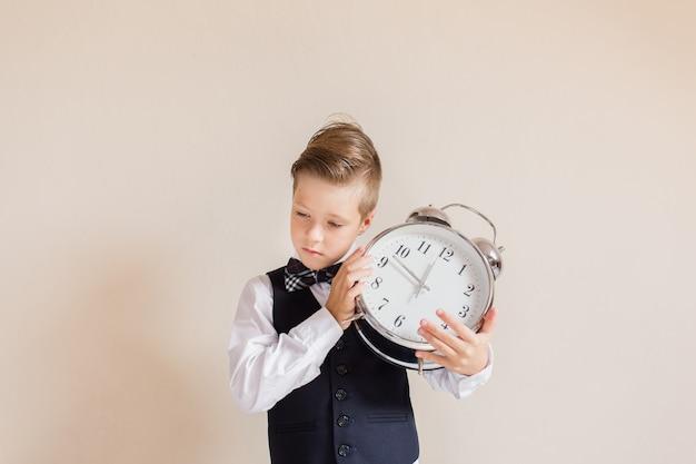 Retrato de niño caucásico en traje gris con gran reloj. lindo niño sosteniendo y escuchando reloj. niño de regreso a la escuela. concepto de educación y tiempo. Foto Premium