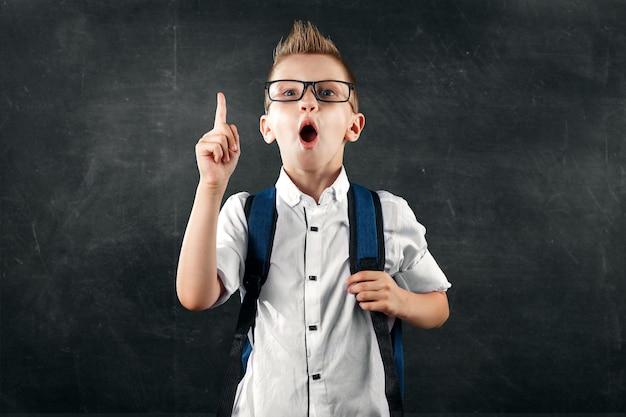 Retrato de un niño de una escuela primaria sobre un fondo de una junta escolar Foto Premium
