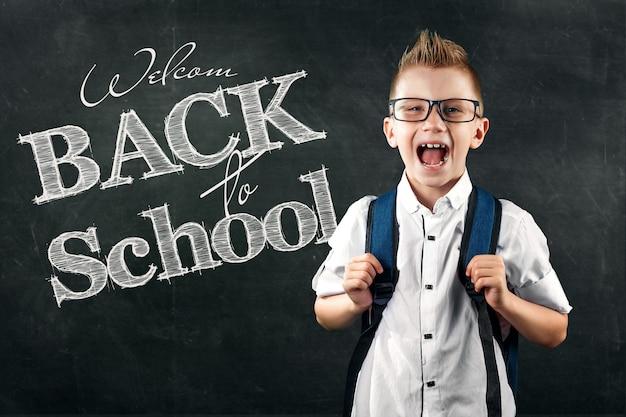 Retrato de un niño de una escuela primaria con el texto regreso a la escuela en una junta escolar Foto Premium