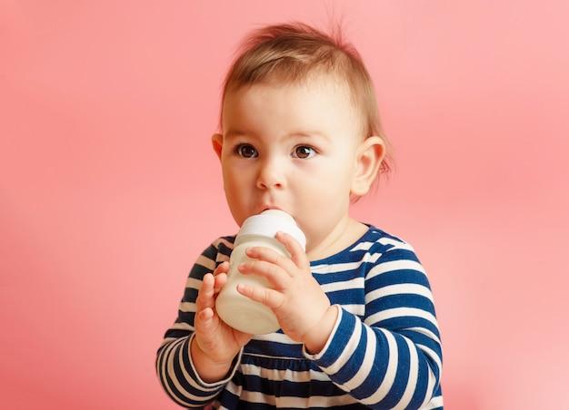 Retrato de un niño lindo bebiendo leche de la botella Foto Premium