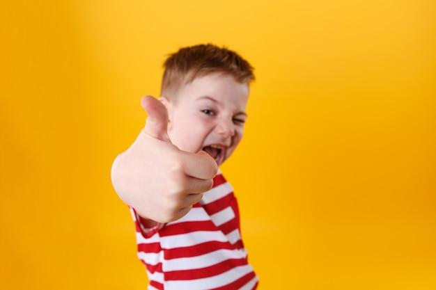 Retrato de un niño pequeño activo sonriente que muestra los pulgares para arriba Foto gratis