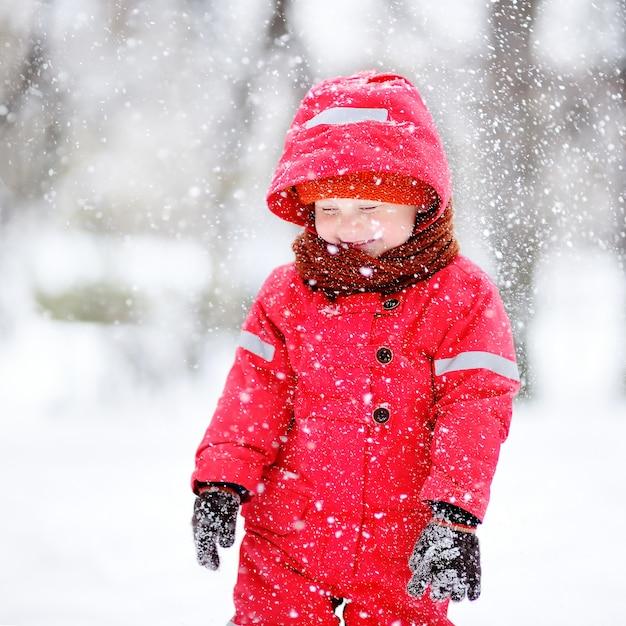 Retrato de niño pequeño en ropa de invierno rojo divirtiéndose con nieve durante las nevadas Foto Premium